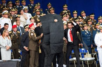 Bodyguards cover the president as drones carrying explosives are shot down close to his platform