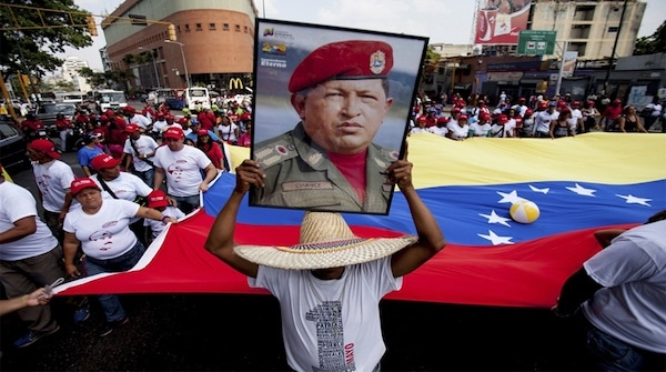 A man holds a giant portrait of Chavez during a rally in Caracas. (AP)
