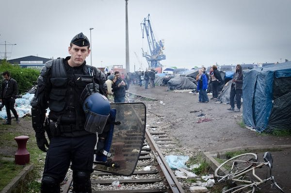 An armed police officer at Calais migrant camp. Photo by Squat le Monde (Photo Credit: Flickr)