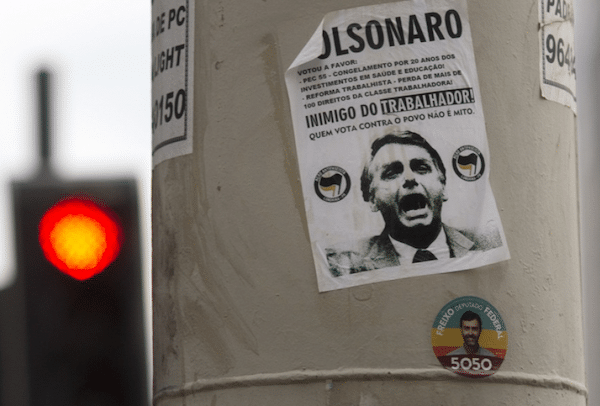 A sticker calling presidential candidate Jair Bolsonaro as an 'Enemy of the worker' covers a street column in Rio de Janeiro, Brazil (Photo Credit: Morning Star)