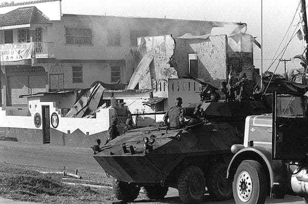 Marines stand guard outside a destroyed Panamanian Defense Force building during the first day of Operation Just Cause, on 20 December, 1989.