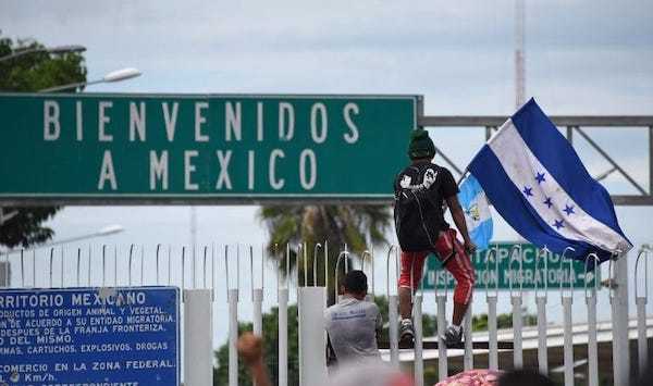 Migrant carrying the Honduran flag makes their way over the Guatemalan-Mexican border fence. (Photo Credit- Peoples Dispatch)