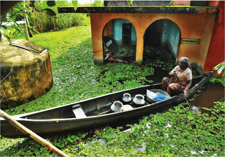 Woman transporting utensils from her flooded house at Kainakari panchayat