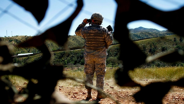 A National Guard soldier glasses the US border with Mexico. Josh Lott | Reuters