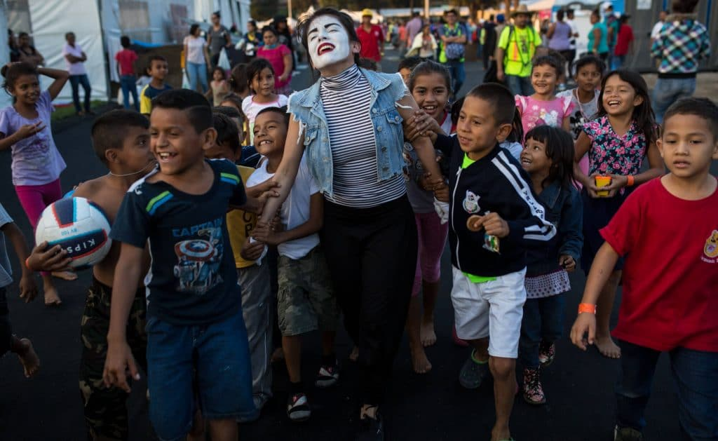 A volunteer performs as a mime for Central American migrant children at the Jesus Martinez stadium in Mexico City, Nov. 6, 2018. Rodrigo Abd | AP