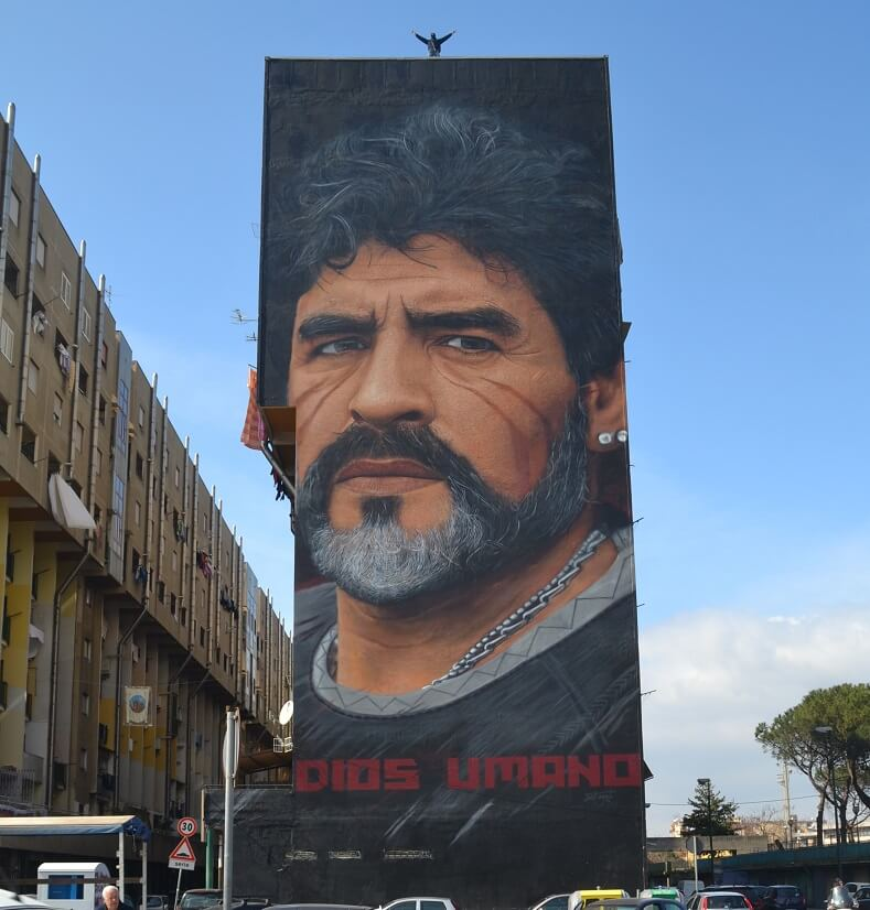 """Diego Armando Maradona. All his images are marked by two red stripes. """"They refer to African magic healing rituals, particularly to the procedure of scarification, initiation rite of the transition from childhood to adulthood that is linked to the symbolic moment of the entry of the individual into the tribe."""" Photo:Jorit"""