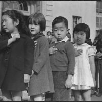 "Header photo: School children reciting the Pledge of Allegiance shortly before the military round-up of Japanese Americans on the West Coast, April 20, 1942. Original caption: ""San Francisco, California. Many children of Japanese ancestry attended Raphael Weill public School, Geary and Buchanan Streets, prior to evacuation. This scene shows first- graders during flag pledge ceremony. Evacuees of Japanese ancestry will be housed in War Relocation Authority centers for the duration. Provision will be effected for the continuance of education."" Photo by Dorothea Lange, courtesy of the National Archives and Records Administration.]"