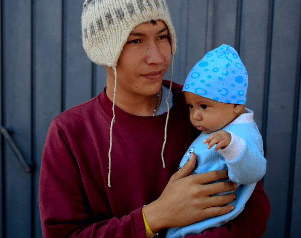 Jose Pedro Rosales Fernandez, 18, from Progreso, Honduras, holds his four-month-old son Dariel, inside the sports complex where thousands of migrants have been camped out for several days in Mexico City, Nov. 9, 2018. Rebecca Blackwell | AP