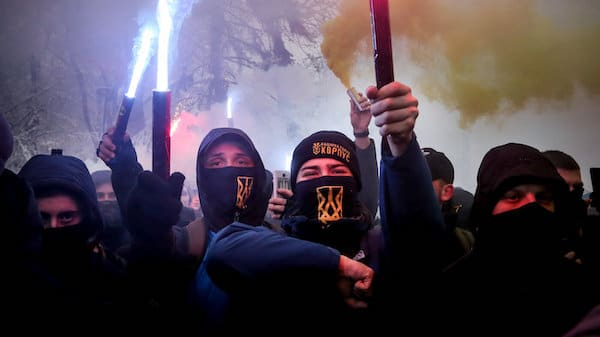 """Volunteers with the right-wing paramilitary Azov National Corps light flares during a rally on the snowy streets in front of the Ukrainian parliament in Kiev, Ukraine, Nov. 26, 2018. Protesters from far-right party National Corps brandished yellow-and-blue flags with the Ukrainian national trident symbol, and a banner reading 'Don't back down!"""" Efrem Lukatsky 