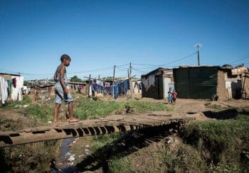 29 May 2018: A child walks across an handmade bridge in the Bhambhayi informal settlement in Durban which has been struggling with poor infrastructure and non- existent service delivery for years. Madelene Cronjé / New Frame