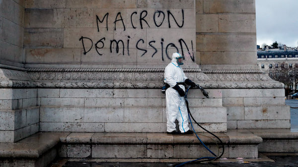 "A worker is about to clean a graffiti reading "" Macron resignation"" on the Arc de Triomphe the day after a protest, in Paris, , Dec. 2, 2018. A protest against rising taxes and the high cost of living turned into a riot in the French capital, as activists torched cars, smashed windows, looted stores and tagged the Arc de Triomphe with multi-colored graffiti. Thibault Camus. 