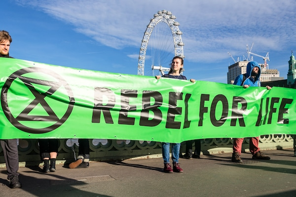 "Extinction Rebellion activists hold a banner reading ""Rebel for life."" Photo Credit- @ Thomas Katan."