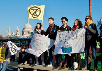 The author, Dr. Claire Wordley (right), joins Extinction Rebellion protesters blocking Blackfriar's Bridge. Diner Ismail waves the Extinction symbol, an hourglass inside a circle representing the planet, over St. Paul's Cathedral in the background. Photo Credit: Jane Carpenter.