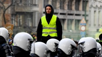 A protestor in a yellow vest stands above police during a demonstration in Brussels, Dec. 8, 2018. Geert Vanden Wijngaert | AP