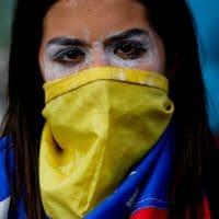 An anti-government protester covers her face with a Venezuelan flag