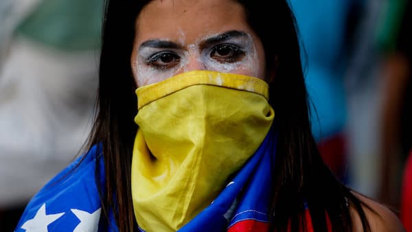 | An antigovernment protester covers her face with a Venezuelan flag | MR Online