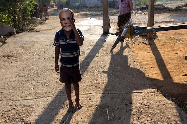 A boy in a Modi mask