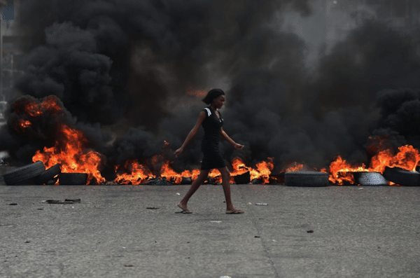If you don't let us breathe, we won't let you breathe. Port-au-Prince, Haiti, 2019. (Photograph: Hector Retamal.)