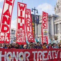 People protesting the Dakota Access Pipeline march past San Francisco City Hall in 2016.  Photo by Pax Ahimsa Gethen [CC BY-SA 4.0 (https-::creativecommons.org:licenses:by-sa:4.0)].