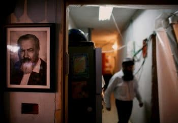 With a portrait of late Jewish extremist leader Rabbi Meir Kahane on the wall, left, a Jewish settler walks inside a disputed building in the West Bank town of Hebron Sunday, Nov. 16, 2008. The four-story building became a flash point for tensions when settlers moved in early last year after claiming to have purchased it from a Palestinian. The Palestinian denies the claim and Israel's highest court ruled Sunday that the Jewish settlers have three days to evacuate the disputed building.. (AP Photo/Dan Balilty)