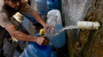 A Caracas resident collects water from the Waraira Repano Hill after the blackout that stopped water pumping in the city