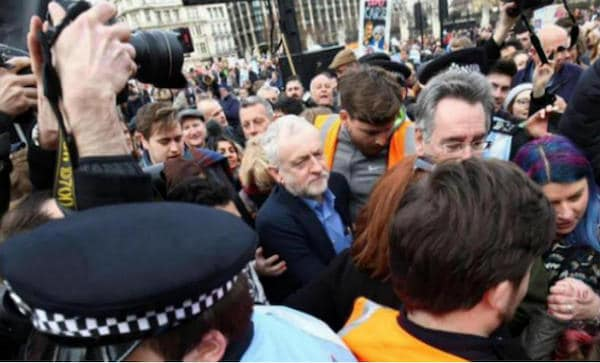 Movement activists, including John Rees, help Jeremy Corbyn back to his car after he spoke at the national demonstration for the NHS on March 6 2017. Photo- Taj Ali