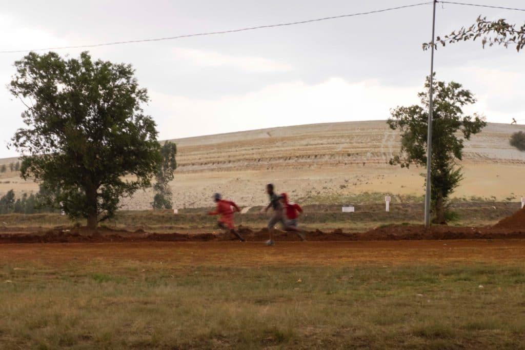 Children running past a gold mine dump in Slovoville outside of Johannesburg, South Africa