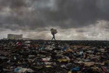 A worker at Agbogbloshie, the world's largest electronic wastedump in Accra, Ghana, carries material through what used to be a wetland area