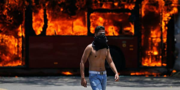 AP photograph of a coup supporter in front of a burning bus (photographer- Fernando Llano).