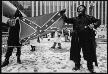 Two men holding Confederate flag © Jon Hughes