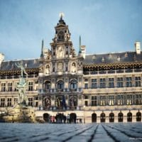 The City Hall (Dutch: Stadhuis) of Antwerp, Belgium, stands on the western side of Antwerp's Grote Markt (Great Market Square). Erected between 1561 and 1565 after designs made by Cornelis Floris de Vriendt and several other architects and artists, this Renaissance building incorporates both Flemish and Italian influences. The City Hall is inscribed on UNESCO's World Heritage List along with the belfries of Belgium and France. Margaret of Parma hands over the keys to the city, by Henri Leys In the 16th century Antwerp became one of the busiest trading ports and most prosperous cities in Northern Europe. The municipal authorities wished to replace Antwerp's small medieval town hall with a more imposing structure befitting the prosperity of the great port city. Antwerp architect Domien de Waghemakere drafted a plan (c. 1540) for a new building in a style typical of the monumental Gothic town halls of Flanders and Brabant. But the threat of war prevented any progress on the project. The building materiasl intended for the city hall were instead used to shore up the city defenses. Not until about 1560 new plans were developed. In the meantime Gothic architecture had gone out of fashion. The new designs for the city hall were in the new Renaissance style. Completed in 1565, the building lasted hardly a decade before being burnt to a shell in the Spanish Fury of 1576. It was restored three years later. The low arcaded ground story is of rusticated stone, and at one time housed little shops. Above are two stories with Doric and Ionic columns separating large mullioned windows, and a fourth story forming an open gallery. The richly ornamented central section, which rises above the eaves in diminishing stages, holds female statues representing Justice, Prudence, and the Virgin Mary, and bears the coats of arms of the Duchy of Brabant, the Spanish Habsburgs, and the Margraviate of Antwerp. Renovations during the late 19th century by architects Pierre Bruno Bourla, Joseph
