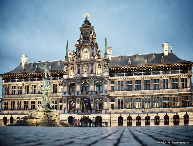 | The City Hall Dutch Stadhuis of Antwerp Belgium stands on the western side of Antwerps Grote Markt Great Market Square Erected between 1561 and 1565 after designs made by Cornelis Floris de Vriendt and several other architects and artists this Renaissance building incorporates both Flemish and Italian influences The City Hall is inscribed on UNESCOs World Heritage List along with the belfries of Belgium and France Margaret of Parma hands over the keys to the city by Henri Leys In the 16th century Antwerp became one of the busiest trading ports and most prosperous cities in Northern Europe The municipal authorities wished to replace Antwerps small medieval town hall with a more imposing structure befitting the prosperity of the great port city Antwerp architect Domien de Waghemakere drafted a plan c 1540 for a new building in a style typical of the monumental Gothic town halls of Flanders and Brabant But the threat of war prevented any progress on the project The building materiasl intended for the city hall were instead used to shore up the city defenses Not until about 1560 new plans were developed In the meantime Gothic architecture had gone out of fashion The new designs for the city hall were in the new Renaissance style Completed in 1565 the building lasted hardly a decade before being burnt to a shell in the Spanish Fury of 1576 It was restored three years later The low arcaded ground story is of rusticated stone and at one time housed little shops Above are two stories with Doric and Ionic columns separating large mullioned windows and a fourth story forming an open gallery The richly ornamented central section which rises above the eaves in diminishing stages holds female statues representing Justice Prudence and the Virgin Mary and bears the coats of arms of the Duchy of Brabant the Spanish Habsburgs and the Margraviate of Antwerp Renovations during the late 19th century by architects Pierre Bruno Bourla Joseph | MR Online