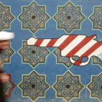 An Iranian cleric walks past mural on the wall of the former U.S. embassy in Tehran