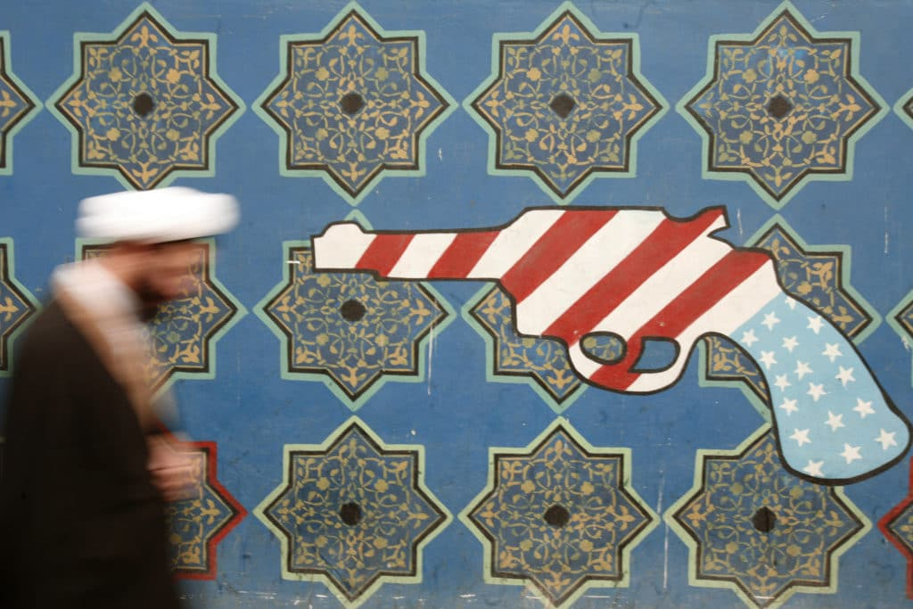 | An Iranian cleric walks past mural on the wall of the former US embassy in Tehran | MR Online