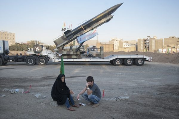 An Iranian couple rest as they sit in front of the Iranian surface-to-surface Zelzal missile while visiting an exhibition to mark the anniversary of the Iran-Iraq war (1980-88) at a Revolutionary Guard Corps military base in northeastern Tehran, September 26, 2011. © Morteza Nikoubazl. Exhibition to mark the anniversary of the Iran-Iraq war (1980-88)