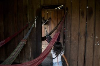 A child runs inside an Uru-Eu-Wau-Wau house in the village of Tribe 623 on June 10, 2019. White settlers in the 1970s waged war on Indigenous tribes and brought in devastating diseases; today there are 200 members of the Uru-Eu-Wau-Wau remaining. Photo: Gabriel Uchida