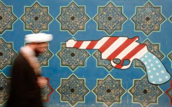 An Iranian cleric walks past a mural on the wall of the former U.S. embassy