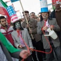 Iranian protestors wear masks as well as hats with the U.S. flag and Israeli flags