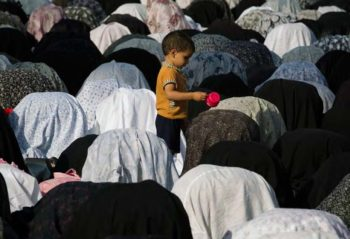 A young Iranian boy plays as his mother prays at the shrine of Hazrat-e Massoumeh