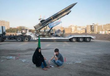 An Iranian couple rests as they sit in front of the Iranian surface-to-surface Zelzal missile
