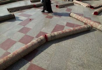 An Iranian woman walks around rolled-up carpets after the festival of Eid-al-Fitr