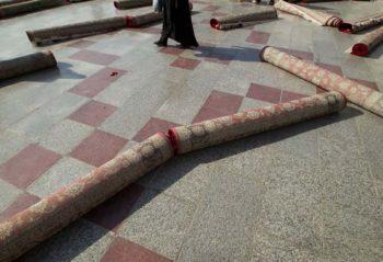 | An Iranian woman walks around rolledup carpets after the festival of EidalFitr | MR Online