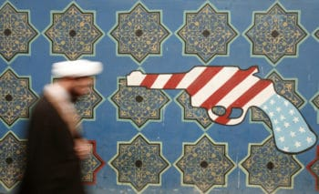An Iranian cleric walks past a mural on the wall of the former U.S. embassy. Tehran, February 2007. Morteza Nikoubazl/Reuters.