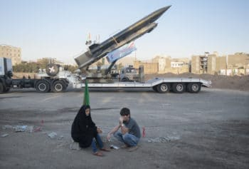 An Iranian couple rest as they sit in front of the Iranian surface-to-surface Zelzal missile while visiting of a war exhibition to mark Iran-Iraq war (1980-88) anniversary at a Revolutionary Guard Corps military base in northeastern Tehran, September 26, 2011.