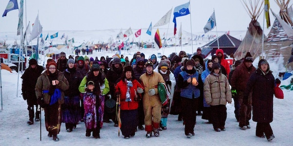 Beatrice Menase Kwe Jackson, center, walks with Daniel Emory, both of the Ojibwe tribe, as they lead a procession to the Cannonball River for a traditional water ceremony at the Oceti Sakowin camp near Cannon Ball, N.D., on Dec. 1, 2016. Photo: David Goldman/AP