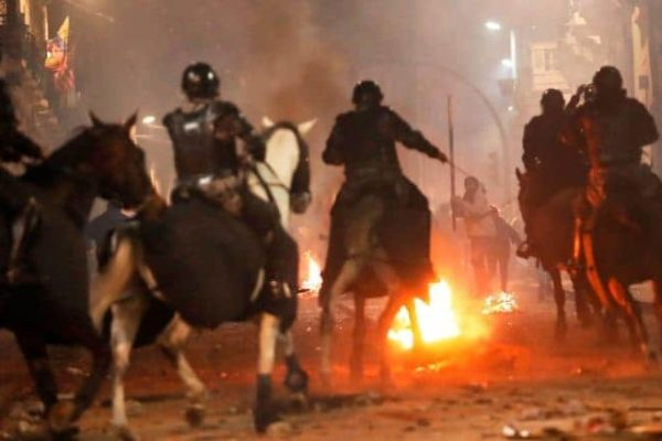Police on horseback advance on protesters near the government palace