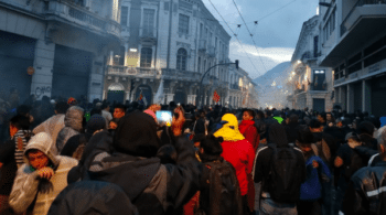 Protesters in Quito's historic center try to protect themselves against police tear gas