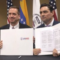 USAID Administrator Mark Green and Carlos Vecchio, Juan Guaidó's representative to the U.S., sign agreement for U.S. money to pay salaries of Venezuela opposition. (AP)