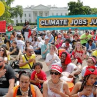 Demonstrators sit on the ground in front of the White House, April 29, 2017, during a demonstration and march. Thousands gathered across the country to march in protest of President Trump's environmental policies, which have included rolling back restrictions on mining, oil drilling, and greenhouse gas emissions at coal-fired power plants.| Pablo Martinez Monsivais / AP