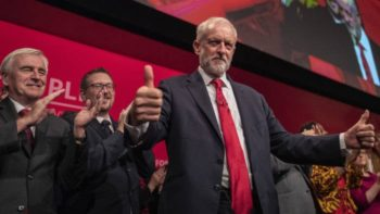 Jeremy Corbyn being applauded and looking pleased with himself after announcing Labour's Medicines for the Many policy at Conference (Financial Times)